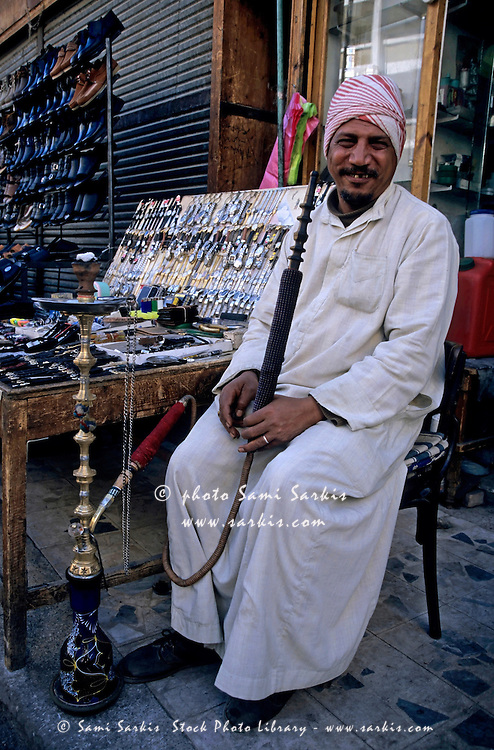Market vendor smoking a hookah in the bazaar, Aswan, Egypt.
