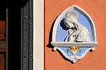 Small statue of the Virgin Mary on a bright orange wall in the small town of Loveno on Lake Como in Italy.