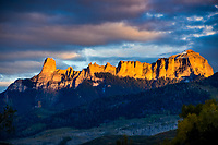 Sunset rays light up Courthouse Mountain and  Chimney Rock which rise above Ridgeway, Colorado in the Cimarron Mountain Range.