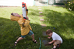 On a hot summer day my sons, ages four and two, play in the water in our backyard. My older son is wearing his rain coat to protect himself from his squirt gun.
