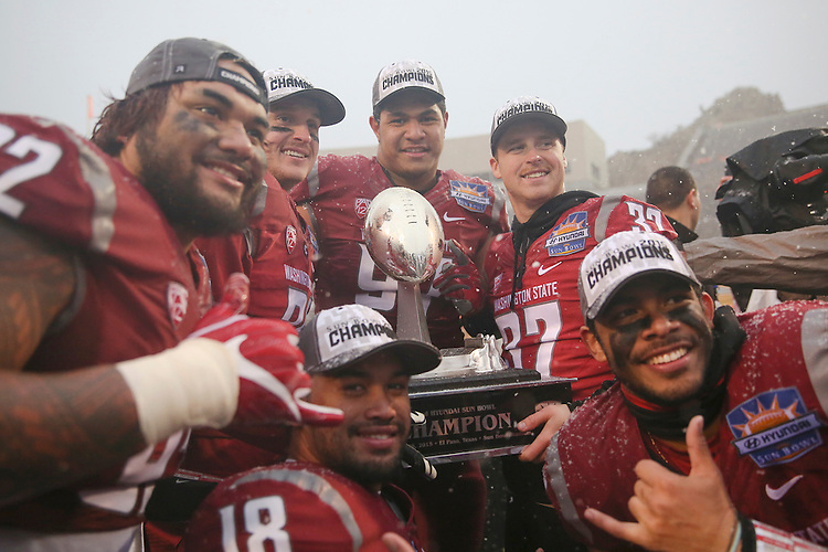 Washington State football players, Robert Barber (92), River Cracraft (21), Destiny Vaeao (97), Skyler Cracraft (37) Taylor Taliulu (30) and Shalom Luani (18), pose for a photo with the Sun Bowl Champions trophy after their Hyundai Sun Bowl game against the Miami Hurricanes in El Paso, Texas, on December 26, 2015.  In a game that could have been named the Snow Bowl instead of the Sun Bowl, WSU took a 20-7 lead in to halftime and then held off a Miami fourth quarter rally to win their first bowl game since the 2003 Holiday Bowl, 20-14.