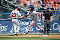 Portland Sea Dogs catcher Austin Rei (28) high fives with hitting coach Lee May (23) as he rounds third base in front of third base umpire Chris Marco after hitting a home run during the first game of a doubleheader against the Reading Fightin Phils on May 15, 2018 at FirstEnergy Stadium in Reading, Pennsylvania.  Portland defeated Reading 8-4.  (Mike Janes/Four Seam Images)
