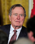 """Former United States President George H.W. Bush listens as U.S. President Barack Obama and first lady Michelle Obama honor him and the other recipients of the 2010 Medal of Freedom, """"the Nation's highest civilian honor presented to individuals who have made especially meritorious contributions to the security or national interests of the United States, to world peace, or to cultural or other significant public or private endeavors"""", in a ceremony in the East Room of the White House in Washington, D.C. on Tuesday, February 15, 2011..Credit: Ron Sachs / CNP"""