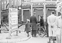 Photo from the NIOD's Huizinga collection. German language series of directional signs on a street corner, partly edged with barbed wire, The Hague (May 6, 1945).