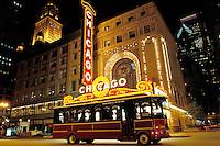 "Party in a trolley bus in front of the Chicago theater in Chicago, Illinois at night. The grandeur of The Chicago Theatre often leaves its visitors breathless. The elegant lobby, majestic staircase and beautiful auditorium complete with murals above the stage and on the ceiling, are components of an amazing building called ""the Wonder Theatre of the World"" when it opened on October 26, 1921...The Chicago Theatre was the first large, lavish movie palace in America and was the prototype for all others. This beautiful movie palace was constructed for $4 million by theatre owners Barney and Abe Balaban and Sam and Morris Katz and designed by Cornelius and George Rapp. Built in French Baroque style, The Chicago Theatre's exterior features a miniature replica of Paris' Arc de Triomphe, sculpted above its State Street marquee. Faced in a glazed, off-white terra cotta, the triumphal arch is sixty feet wide and six stories high. Within the arch is a grand window in which is set a large circular stained-glass panel bearing the coat-of-arms of the Balaban and Katz chain - two horses holding ribbons of 35-mm film in their mouths...The grand lobby, modeled after the Royal Chapel at Versailles, is five stories high and surrounded by gallery promenades at the mezzanine and balcony levels. The grand staircase is patterned after that of the Paris Opera House and ascends to the various levels of the Great Balcony...The 3,600 seat auditorium is seven stories high, more than one half of a city block wide, and nearly as long. The vertical sign ""C-H-I-C-A-G-O,"" at nearly six stories high, is one of the few such signs in existence today. A symbol of State Street and Chicago, the sign and marquee are landmarks in themselves, as is the 29-rank Wurlitzer theatre pipe organ."