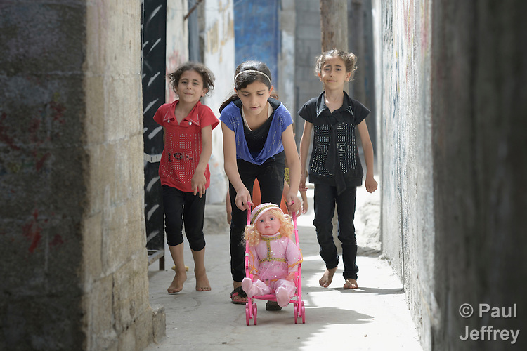 Girls play in a narrow street in the Al-Shalti refugee camp in Gaza. Residents of the Palestinian territory are still reeling from the death and destruction of the 2014 war with Israel, and the continuing siege of the seaside territory by the Israeli military.