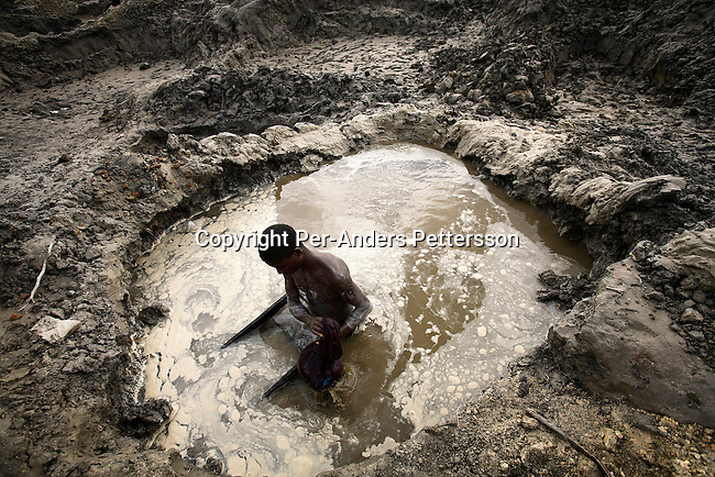 LUBUMBASHI, DEMOCRATIC REPUBLIC OF CONGO - DECEMBER 13: A young boy looks for copper standing in a pit on December 13, 2005 in Ruashi mine about 20 kilometers outside Lubumbashi, Congo, DRC. They are some of about 4,000 young men and children that work as artisan miners. Children as young as eight years old work in the mine under dangerous conditions.  Every month a few of the miners are killed. Congo has one of the largest Copper deposits in the world and most of it is exported to China. It?s fueling the thirst for minerals for China?s economic boom. The young men who works in the mine makes a few US dollars a day, and the children much less. The mine is about one hundred years old and has been a source of wealth for the Katanga province for many years. In recent years many foreign companies and shady business people has moved into Congo to plunder its wealth. The country has no elected government and the corruption is rife. Border and customs officials are easily bribed. Congo has had a civil war since 1997 and it?s estimated that nearly 4 million people has died in fighting and because of lack of health care. .(Photo: Per-Anders Pettersson/Getty Images).