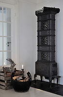 A tall cast iron stove from a bedroom in the old farmhouse was restored and installed in the new house