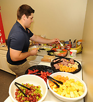 NWA Democrat-Gazette/ANDY SHUPE<br /> Tyler Burson, a Har-Ber graduate and current Northwest Arkansas Community College student, arranges food Wednesday, Aug 9, 2017, for the visiting Midland Rockhounds while performing his duties as the clubhouse assistant for the Northwest Arkansas Naturals at Arvest Ballpark in Springdale.