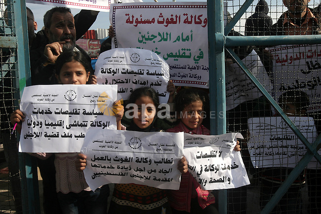 Palestinian children hold banners during a protest against the UNRWA decision to reduce of the food aid in front of the headquarters United Nations Relief and Works Agency (UNRWA) in Rafah southern Gaza city, on Jan. 11, 2014. Photo by Eyad Al Baba