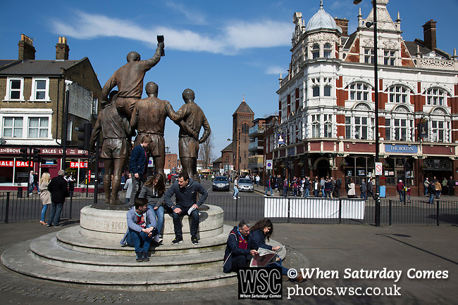 West Ham United 2 Crystal Palace 2, 02/04/2016. Boleyn Ground, Premier League. Fans sitting at the World Cup statue on Barking Road, with the Boleyn pub, a regular gathering place for home fans, in the background before West Ham United hosted Crystal Palace in a Barclays Premier League match at the Boleyn Ground. The Boleyn Ground at Upton Park was the club's home ground from 1904 until the end of the 2015-16 season when they moved into the Olympic Stadium, built for the 2012 London games, at nearby Stratford. The match ended in a 2-2 draw, watched by a near-capacity crowd of 34,857. Photo by Colin McPherson.