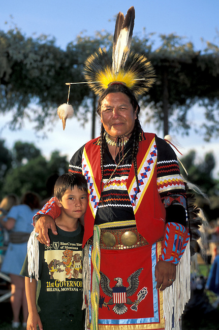 Blackfeet man in traditional dress mentors youth on Blackfeet Reservation puts arm around young boy during an American Indian gathering, Montana