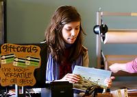 Arkansas Democrat-Gazette/JASON IVESTER 12-19-07<br />Lisa Sharp's daughter, Elizabeth Sharp, 16, scans books for a customer purchase at Nightbird Books in Fayetteville Wednesday.