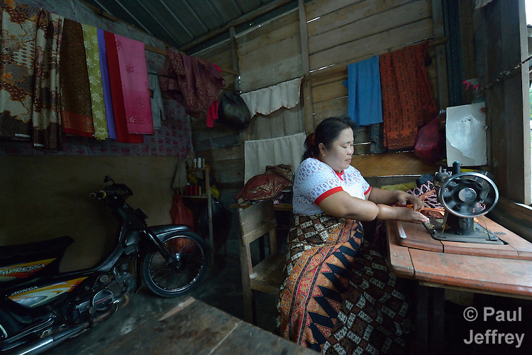Misbah Teleumbanua sews on a sewing machine in her home in Gamo, a village on the Indonesian island of Nias. Teleumbanua lost one leg as a baby, and spent most of her life hopping around on the other leg. Then following the 2005 earthquake on Nias, a mobile team from YEU, an ACT Alliance member agency, came to her neighborhood looking for people who'd been left disabled by the quake. They told her they'd help her as well. She learned to use crutches and was fitted with a proper prosthesis, then took a three-month tailoring class which allowed her to open her own business sewing clothes for her neighbors.