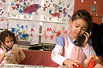 Preschool Headstart 3-5 year olds pretend play area girl in dressup outfit talking on telephone another girl talking on phone in background horizontal