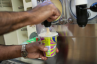 A 7-Eleven employee dispenses Slurpees to hordes of customers in a 7-Eleven store in New York on Friday, July 11, 2014 (7-11, get it?), Free Slurpee Day! The chain has been giving away free 7oz Slurpees for the past twelve years on July, 11, which it has adopted as its corporate birthday. The popular icy, slushy, syrupy drinks are available in regular and diet flavors, in combinations, and the stores have stocked up with extra barrels of syrup to meet the expected demand. The 87 year old chain expects to serve over 7 million Slurpees today. (© Richard B. Levine)
