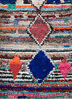 A colourful rag rug with a diamond pattern.