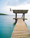 HONDURAS, Roatan, boy jumping off pier to get his soccer ball