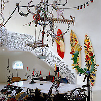 The staircase balustrade and surf boards have been decorated by Keith Haring, while one of Jean Tinguely's sculptural machines hangs above the table
