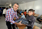 Josef Pfattner (left), a regional executive for the Geneva-based ACT Alliance, hands over a school uniform to a boy in the Zaatari Refugee Camp, located near Mafraq, Jordan. Opened in July, 2012, the camp holds upwards of 50,000 refugees from the civil war inside Syria, but its numbers are growing. International Orthodox Christian Charities and other members of the ACT Alliance are active in the camp providing essential items and services.