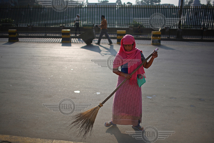 Woman cleaning the road in the early morning.