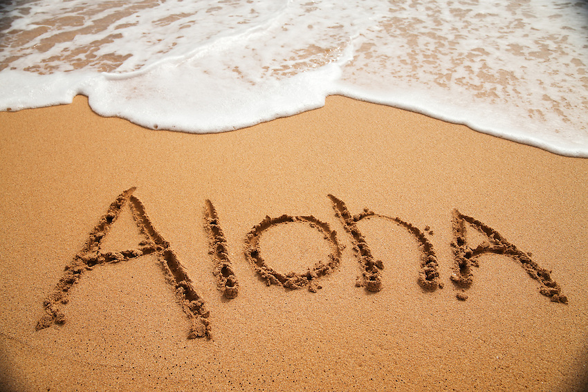 """Inviting """"Aloha"""" written in soft beach sand with surf approaching."""