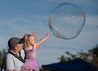NWA Democrat-Gazette/J.T. WAMPLER Sean Dempsey of Fayetteville holds his daughter Ada, 2, while she stretches to touch a soap bubble during the annual Firefly Fling Saturday July 15, 2017 at the Botanical Garden of the Ozarks. The event also included garden fairies, food trucks, glowing games, fairy house building, fire dancing, nature stations and puppet performances.