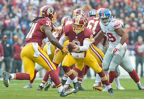 Washington Redskins quarterback Kirk Cousins (8) looks to hand-off to running back Matt Jones (31) in first quarter action against the New York Giants at FedEx Field in Landover, Maryland on Sunday, November 29, 2015. Pursuing on the play is New York Giants outside linebacker Devon Kennard (59).  The Redskins won the game 20-14.<br /> Credit: Ron Sachs / CNP<br /> (RESTRICTION: NO New York or New Jersey Newspapers or newspapers within a 75 mile radius of New York City)