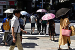 Pedestrians in the Ginza shopping district shelter from the sun with parasols on August 9, 2019 in Tokyo, Japan. Japan's capital recorded its 17th consecutive day since July 24th with temperatures over 31C. (Photo by Marie Froger/AFLO)