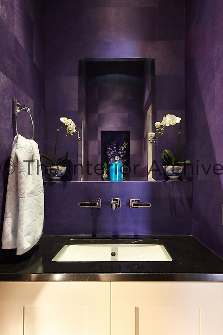 A hand basin is set in a cupboard unit. The walls are covered in a deep purple wallpaper.