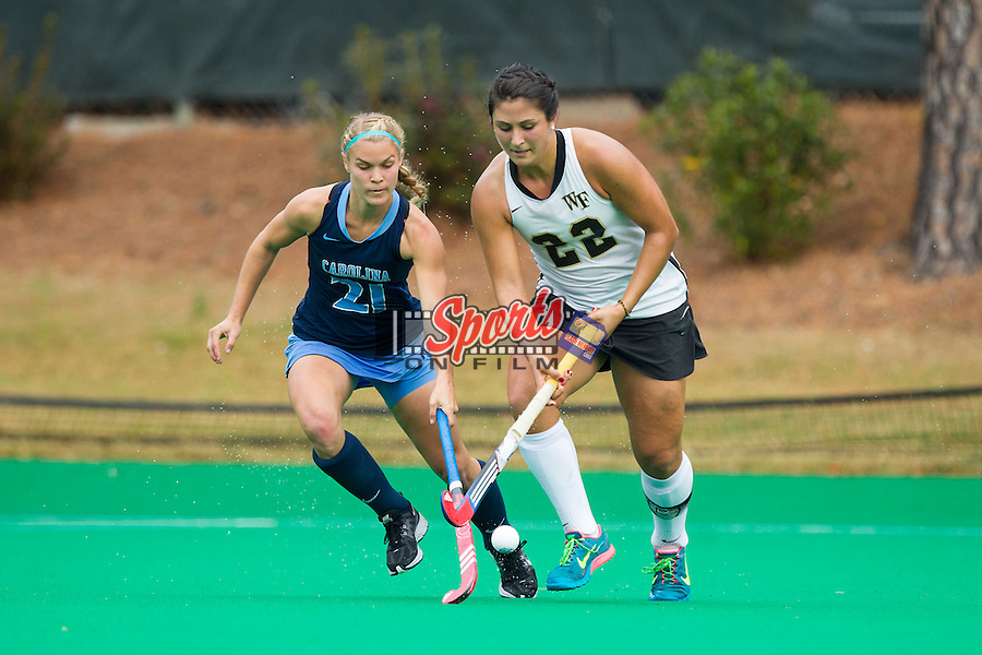 Anna Kozniuk (22) of the Wake Forest Demon Deacons keeps the ball away from Casey Di Nardo (21) of the North Carolina Tar Heels during Second Round action in the 2013 NCAA Field Hockey Championship at Francis E. Henry Stadium on November 17, 2013 in Chapel Hill, North Carolina.  The Tar Heels defeated the Demon Deacons 5-2. (Brian Westerholt/Sports On Film)