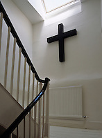 Continuing the black and white theme of this house, a black crucifix hangs on a wall of the white staircase