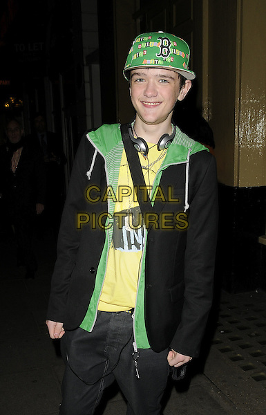 """GEORGE SAMPSON.The """"Oliver!"""" press night afterparty, Waldorf Hilton Hotel, Aldwych, London, England..January 14th, 2009.half length black jeans denim jacket green hat lining baseball cap headphones.CAP/CAN.©Can Nguyen/Capital Pictures."""