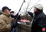 "Waterbury, CT-07 December 2012-120712CM01-  Mike Fox, a U.S Navy Vietnam Veteran, back, Doc Docchio, member of the Waterbury Veterans Memorial Committee, left and Bob Batters of Waterbury, lower the ""USS Never Sailed"" into the Naugatuck River Friday afternoon in Waterbury.  The trio were apart of a remembrance put on by the Waterbury Veterans Memorial Committee, which honored Pearl Harbor Day by lowering a wreath basket into the Naugatuck River from the Pearl Harbor Memorial Bridge on Freight Street.        The event was apart of the Committee's Pearl Harbor Remembrance Day which also included Patriotic Services, held at the BPOE Elks Club in Waterbury. Christopher Massa Republican-American"