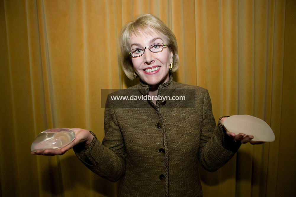 20 November 2006 - New York City, NY - Dr Roxanne J. Guy, President of the American Society of Plastic Surgeons poses holding a textured silicon gel implant (right) and a saline smooth implant (left) during a press event in New York City, USA, 20 November 2006. The FDA earlier rescinded a 14-year ban on silicone gel implants for cosmetic breast enhancement. Silicone implants are available in most other countries, where they have quickly replaced the saline-filled alternatives. Photo Credit: David Brabyn.