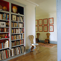 Recessed bookshelves line the walls of this upstairs hallway which is furnished with a collection of wooden hall chairs and framed prints of classical architectural details