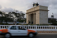 A taxi passes Independence Arch, Independence Square.