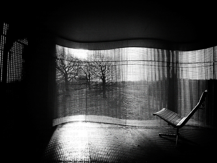 A room with wire mesh walls, with 60's chair, overlooking forest.
