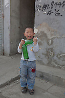 A boy plays with beer bottles in front of his home at Dawangjing Village which is being demolished on April 9, 2009 on the outskirts of Beijing, China. The local authorities are evicting residents, who are mainly migrant workers, to redevelop the area. The redevelopment of Beijing continues in high speed.