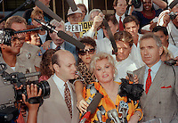 Zsa Zsa Gabor talks with the media outside the courthouse in Beverly Hills, Sept. 30, 1989, after she was found guilty of slapping a motorcycle cop.  Gabor's attorney, William Graysen is at left and her husband Frederick von Anhalt is at right. (Photo by Alan Greth)