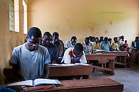 Adults read during adult literacy class for former IDPs, organized by Ugandan NGO Literacy and Adult Basic Education (LABE). Many people who spent years in camps for internally displaced persons (IDPs) never had a chance to attend school. Ayima Primary School, Amuru Subcounty, Amuru District.