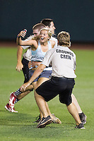 Unidentified female fan is grabbed by stadium security after she ran onto the field during the eighth inning of the 2013 Men's College World Series Final on June 25, 2013 at TD Ameritrade Park in Omaha, Nebraska. The UCLA Bruins defeated the Mississippi State Bulldogs 8-0, winning the National Championship. (Andrew Woolley/Four Seam Images)