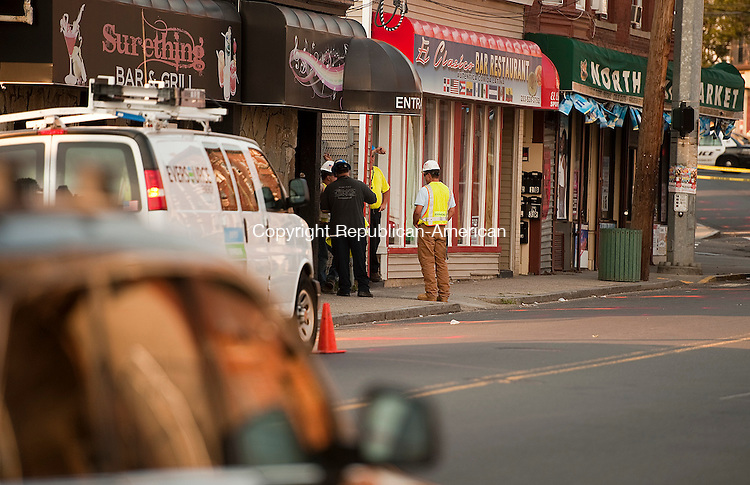 WATERBURY, CT--- -081715JS02- Workers from Eversource Energy look for the cause of a possible underground explosion Monday afternoon on North Main Street in Waterbury. The road was closed and traffic detoured as they investigated. <br /> Jim Shannon Republican-American