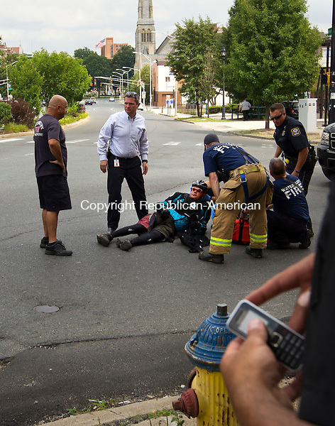 Waterbury, CT- 01 July 2014-070114CM01- Waterbury emergency services, help Ramon Rosario of Waterbury, at the intersection of West Main and Meadow Streets in Waterbury on Tuesday.  Rosario said he was struck while riding his bicycle, by a motor vehicle after turning right onto Meadow Street. Rosario said he was OK and was fortunate to have not have been injured.  The Waterbury Police Department is investigating the incident.     Christopher Massa Republican-American