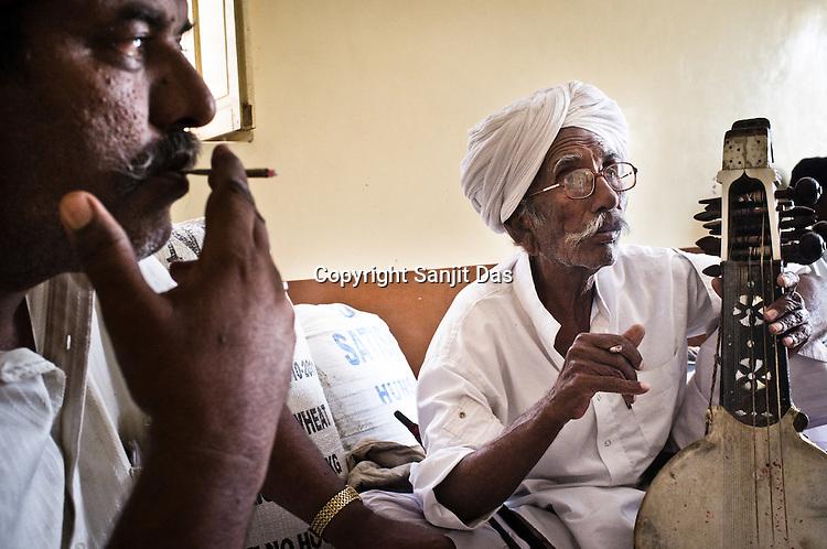 75-year-old Manganiyar artist, Saqar Khan and his son, Ghewar Khan (left) takes a break and smoke biri (local cigarette) inbetween field recordings inside their house in Hamira village of Jaiselmer district in Rajasthan, India. Photo: Sanjit Das/Panos