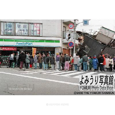 January 17th, 1995 : Kobe, Japan - People wait in line for food and provisions at a convenience store. (Photo by Kenji Onishi)