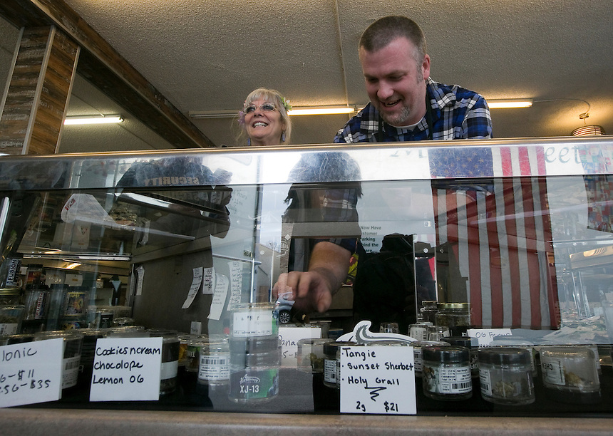 Budtenders Cher Poff (L) Wes McLeod arrange items in a case at Main Street Marijuana in downtown Vancouver February 14, 2017. (Photo by Natalie Behring for the Columbian)