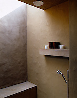 This contemporary shower has walls of adobe and is naturally lit by a skylight