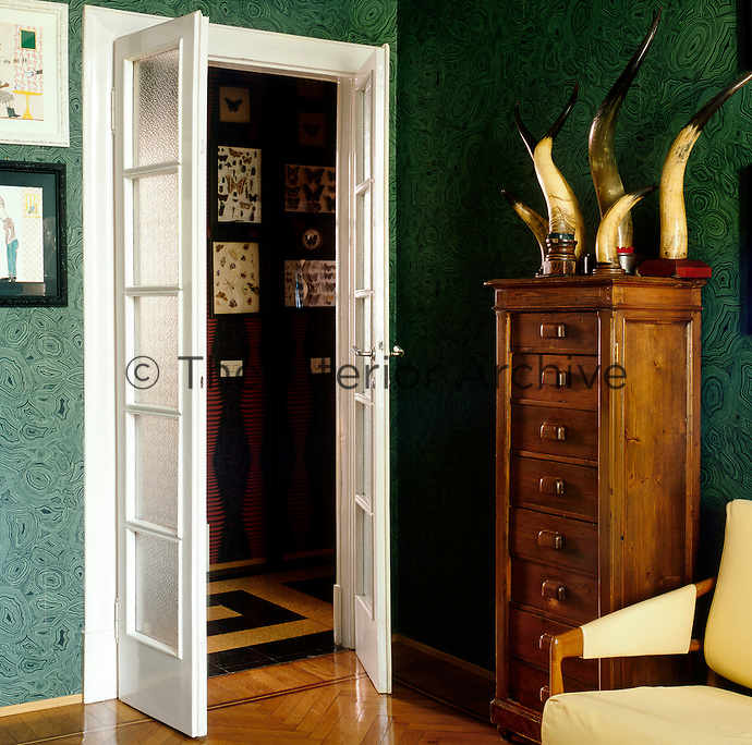A pair of French doors connects the hallway to the sitting room where the green and black pattern wallpaper and parquet floor create an elegant decor. To one side, a collection of animal horns sits atop a wooden chest of drawers.