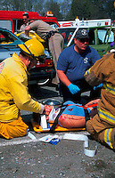 Rescue workers practice attending to an injured person at a simulated drunk driving accident.